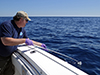 Bob Nelson using teflon dip net to collect oil from surface of Gulf of Mexico