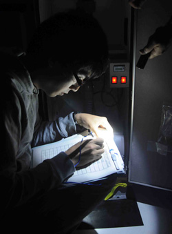 By flashlight on the upper deck, Hiroomi Miyamoto from Tokyo University pours through the Japanese version of the aerosol sampler operating instructions to determine why a sampler on board would not start.