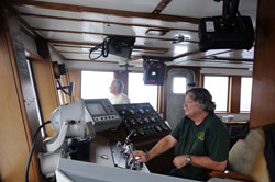 Capt. Clary Gutzeit (right) and Able-Bodied Seaman George Longshore keep the 8-to-noon watch in the pilothouse as the weather worsens.