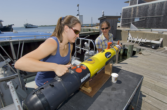 Working at the WHOI dock, summer student fellow Tess Brandon (Cornell University) and WHOI engineering assistant Amy Kukulya prepare a REMUS autonomous underwater vehicle for a research trip out to the waters off Martha's Vineyard. Working with physical oceanographer Al Plueddemann, Brandon studied the hydrodynamics of a submarine sand ridge.