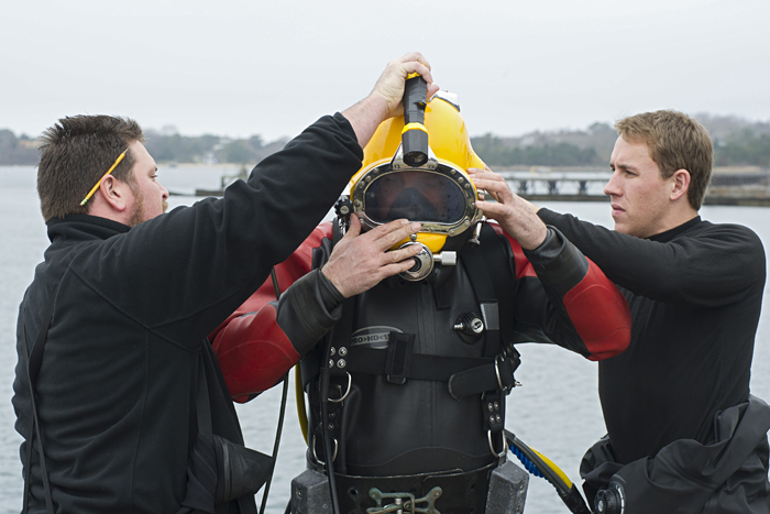 Assistant marine ops coordinator Chad Smith and Julian Schanze, a graduate student in the MIT/WHOI Joint Program, help Dive Officer Ed O'Brien into his hardhat diving gear.