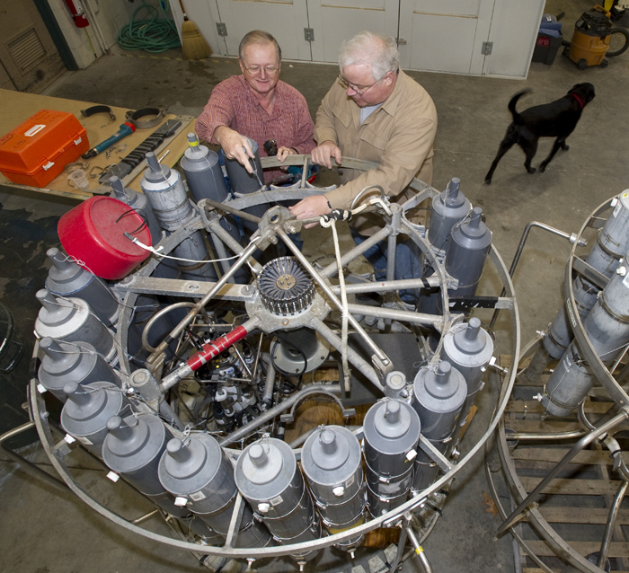 Research associates George Tupper (left) and Marshall Swartz check a CTD rosette, which measures the salinity and temperature of seawater at various depths, as Swartz's dog Little Bear takes a break.