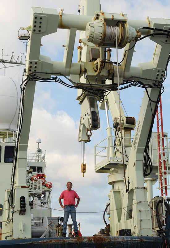 Senior research specialist Jim Broda stands under the long core deployment mechanism on R/V Knorr as the ship sits at the WHOI dock in September 2009.