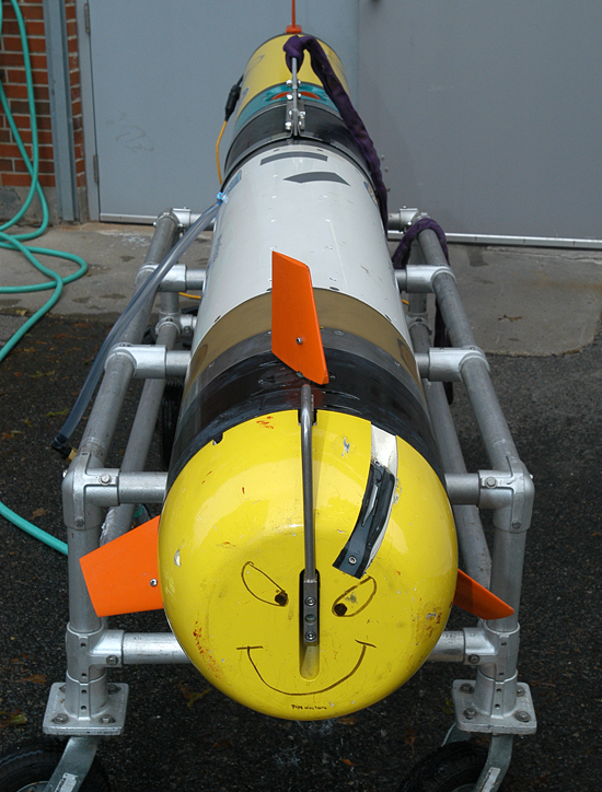 A REMUS-600 autononomous underwater vehicle sits on its cradle outside the Oceanographic Systems Lab. The AUV, which can dive to 600 meters, has a modular design to accommodate varying payloads and sensors. That large white section of the vehicle is the Small Synthetic Aperture Minehunter (SSAM), a high-resolution imaging sonar.