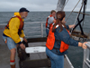 Hovey Clifford helps two summer student fellows deploy a grab sampler