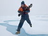 John Kemp leaping across ice gap carrying drill bits for ITP deployment.