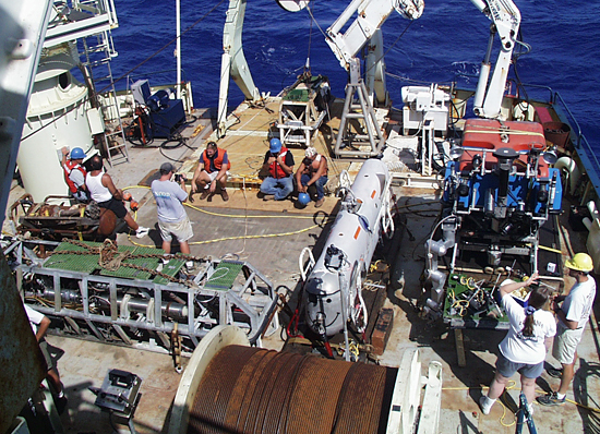 Scientific gear and underwater vehicles crowd the fantail