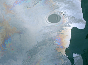 A fresh oil slick from the Deepwater Horizon spill, during June 2010.  Note that one drop of detergent was added to the oil slick, forming the cleared circle.