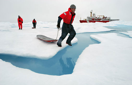 WHOI engineer Kris Newhall jumps across a melt pond
