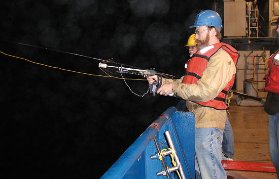 WHOI biogeochemist Ken Buesseler uses a crossbow to retrieve a Neutrally Buoyant Sediment Trap after one of its missions in the depths.