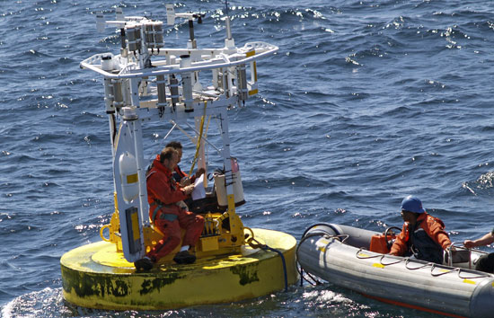 Members of the WHOI Upper Ocean Processes Group conduct at-sea repairs on an ASIMET buoy in the Gulf Stream that was probably damaged by a ship.