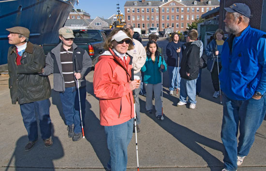 Amy Bower (orange jacket) leads a group of visiting students from Perkins School for the Blind on a tour of the WHOI dock, aided by WHOI senior engineering assistant Hovey Clifford (blue) and Exhibit Center volunteer Sheldon Holzer (in cap).