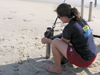 Elizabeth Halliday attaches winch collar to coring tube on beach in Duck, NC