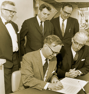 Aboard the research vessel Chain, MIT President Howard W. Johnson (left) and WHOI Director Paul Fye sign the memorandum of agreement that created the MIT/WHOI Joint Program on May 8, 1968. In the back row are (left to right): WHOI Dean of Graduate Studies H. Burr Steinbach, MIT Provost Jerome Wiesner, and Frank Press, head of MIT?s Earth Science Department.