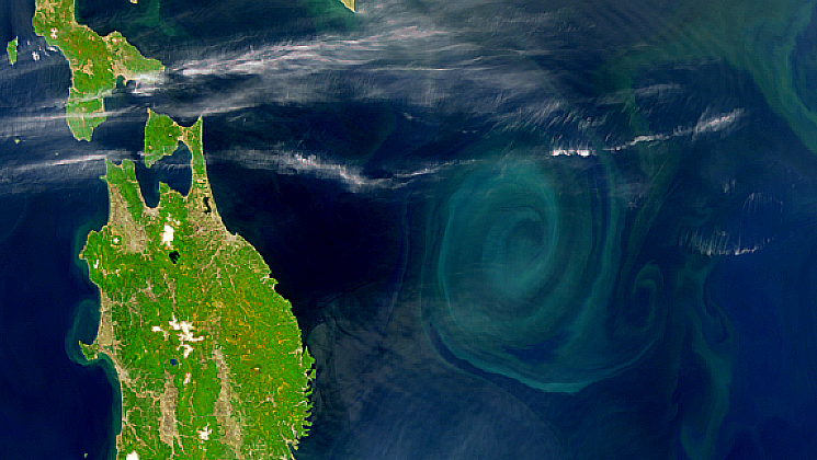 A very well-defined spiral eddy is visible through the haze off the east coast of Japan.