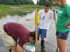 Postdoctoral Fellow Jed Goldstone (left) teaches Summer Student Fellows Thiago Parente (center) and Katie Barott to sample killifish.