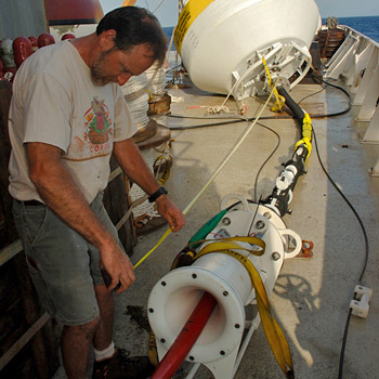 Senior engineering assistant Jeff Lord examines pieces of a new inductive-telemetry buoy that WHOI researchers deployed off of Barbados in April 2007.