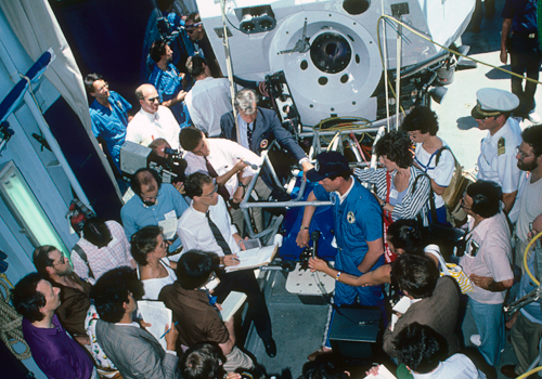 Reporters mob WHOI scientist Bob Ballard to hear what the 1986 expedition found.