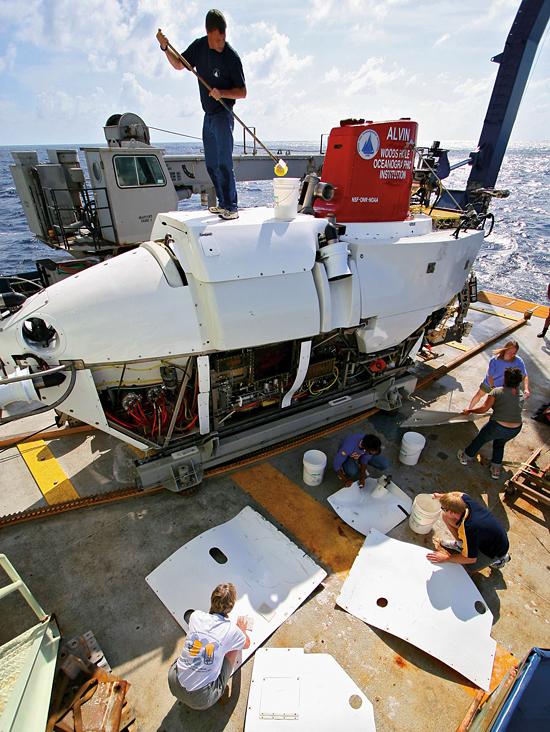 Working on the deck of the research vessel Atlantis, pilots and technicians from the Alvin Group scrub down the submersible between dives.