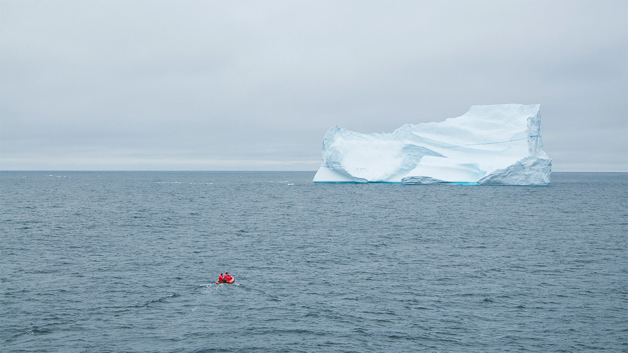 Tiny boat approaches big iceberg.