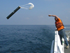 Dave Morton throwing overboard a sonobuoy hydrophone receiver.