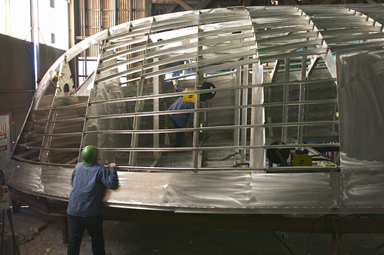 Workers at Gladding-Hearn Shipbuilding assemble the aluminum hull of Tioga.
