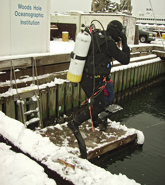 scuba diver jumping off WHOI dock in winter