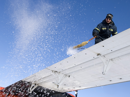 Travis Goetzinger sweeps the frost off of the wings of the Twin Otter in preparation for takeoff.