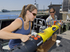 Summer Student Fellow Tess Brandon and Engineering Assistant Amy Kukulya working with a REMUS at the dock.