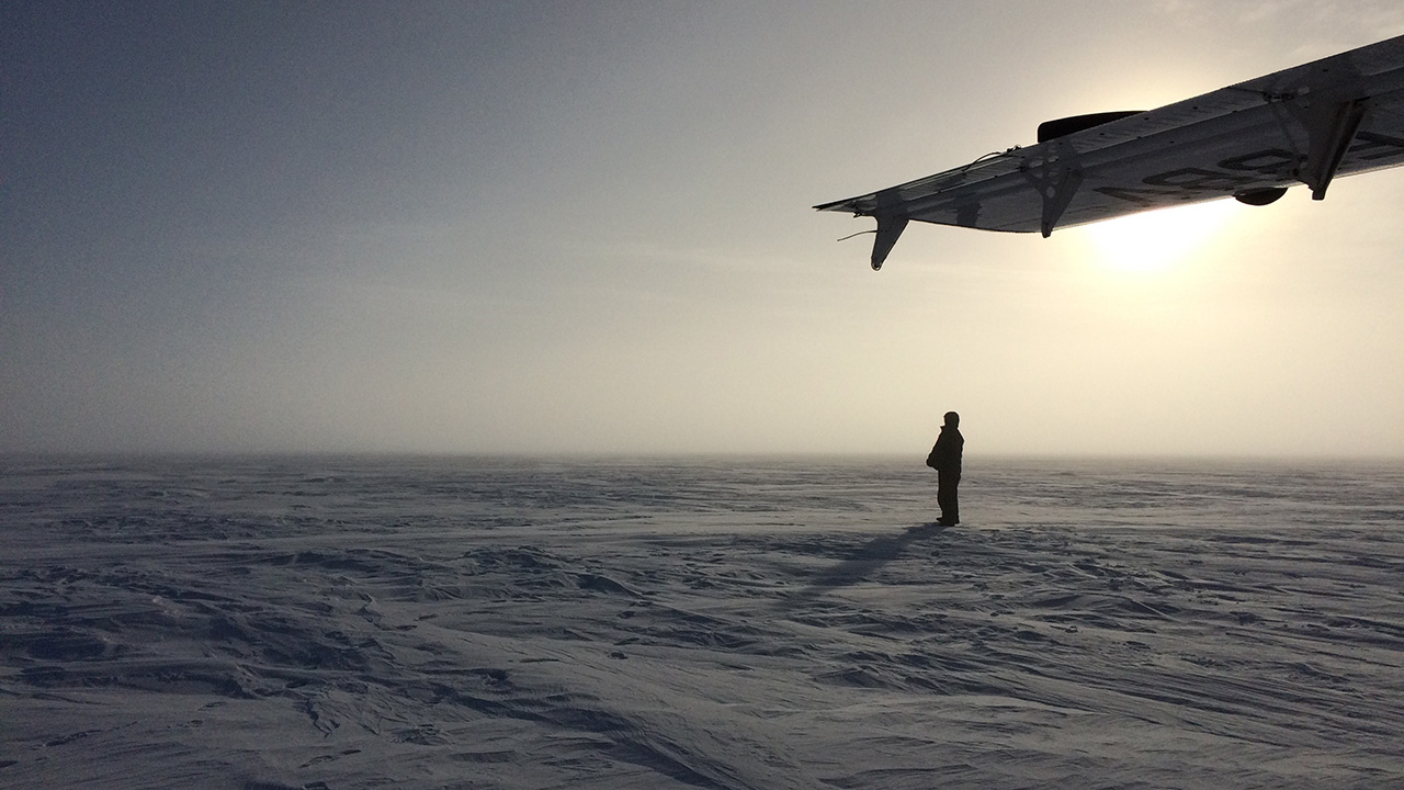 Researcher in Antarctica waits for plane.