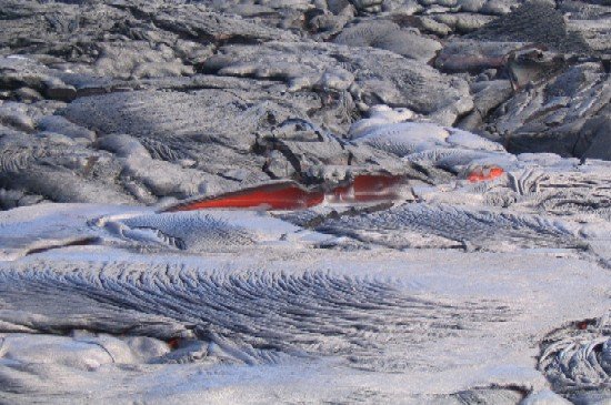 Fresh lava makes beautiful glowing landscapes. Here lava is emerging from beneath a solidified crust and pooling in nearby shallow depressions.