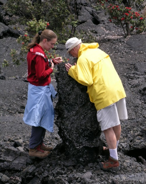 ad and Jessica Williams peer down a ?tree mold?. Tree molds form when active lava flows surround and quench against trees.