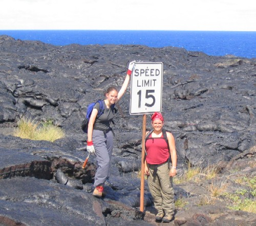 Margaret Boettcher and Jessica Williams assist the Kilauea Police Department in enforcing strict speed limits on lava flows.  In actuality, this sign once marked the speed limit on a coastal highway that was covered by lava during the current Pu?u ?O?o-Kupaianaha eruption.