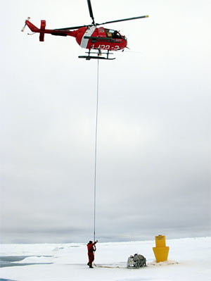 attaches the helicopter sling to a winch for transport back to the icebreaker
