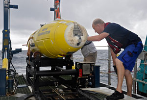 Fred Wendt  of IFM Geomar and WHOI research specialist Mark Dennett (partially hidden) inspect the  REMUS 6000 autonomous underwater vehicle owned by the WAITT Institute as it is positioned on the LARS (Launch and Recovery System) during the April 2011 search for Air France Flight 447.