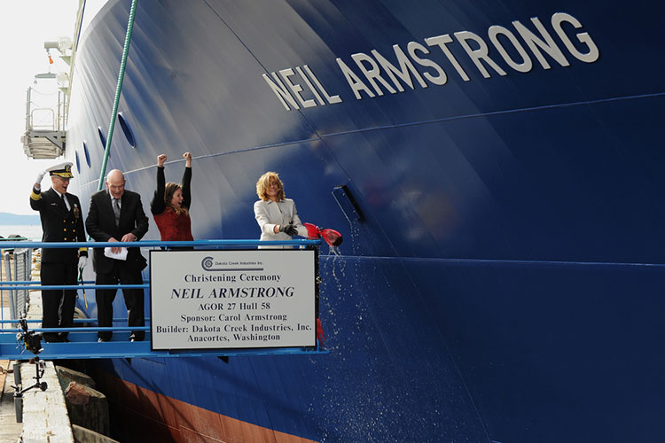Carol Armstrong, ship's sponsor for the Auxiliary General Oceanographic Research (AGOR) research vessel (R/V) Neil Armstrong (AGOR 27), breaks a bottle across teh bow during a christening ceremony at Dakota Creek Industries, Inc., shipyard in Anacortes, WA