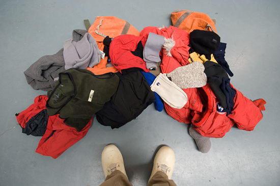 Pile of warm clothing set out on the floor.