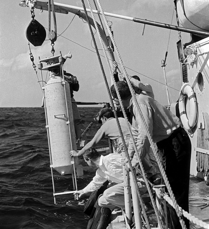 researchers on ship with person-sized sampling bottle
