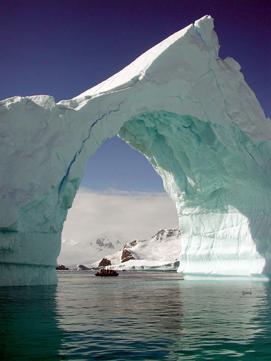 A zodiak boat carries a group of WHOI Associates and other ecotoursts through an iceberg arch off Antarctic