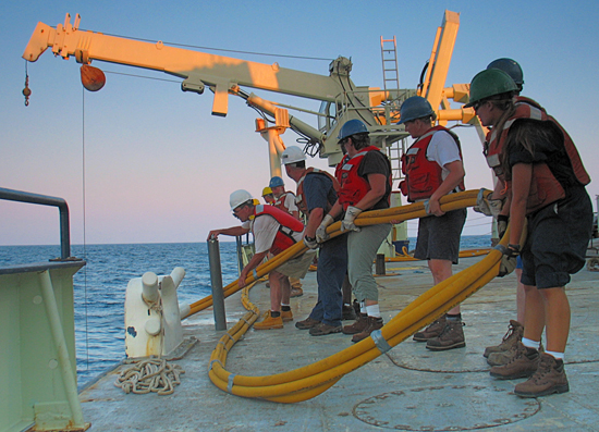 Chief Scientist John Goff (blue t-shirt and jeans) and other science staff are deploying a Vibracorer off the R/V Knorr.
