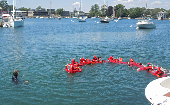 water safety students in Gumby suits form human chain to stay together in the water