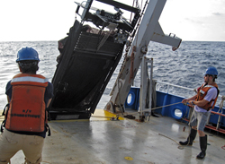 The massive metal frame connected to long collecting nets isn?t easy to handle. Here, WHOI summer student Jon Fincke (right) and University of Connecticut grad student Paola Batta-Lona take the lines to help guide the MOCNESS computer-controlled net system over the stern of R/V Connecticut in July 2010. WHOI biologists Gareth Lawson and Peter Wiebe led the cruise in the Atlantic to investigate physical factors leading to krill aggregations in canyons at the edge of the continental shelf and the importance of these aggregations to the marine food web.