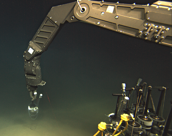 ROV Jason's manipulator arm inserts an injection pushcore into the seafloor near a DHAB