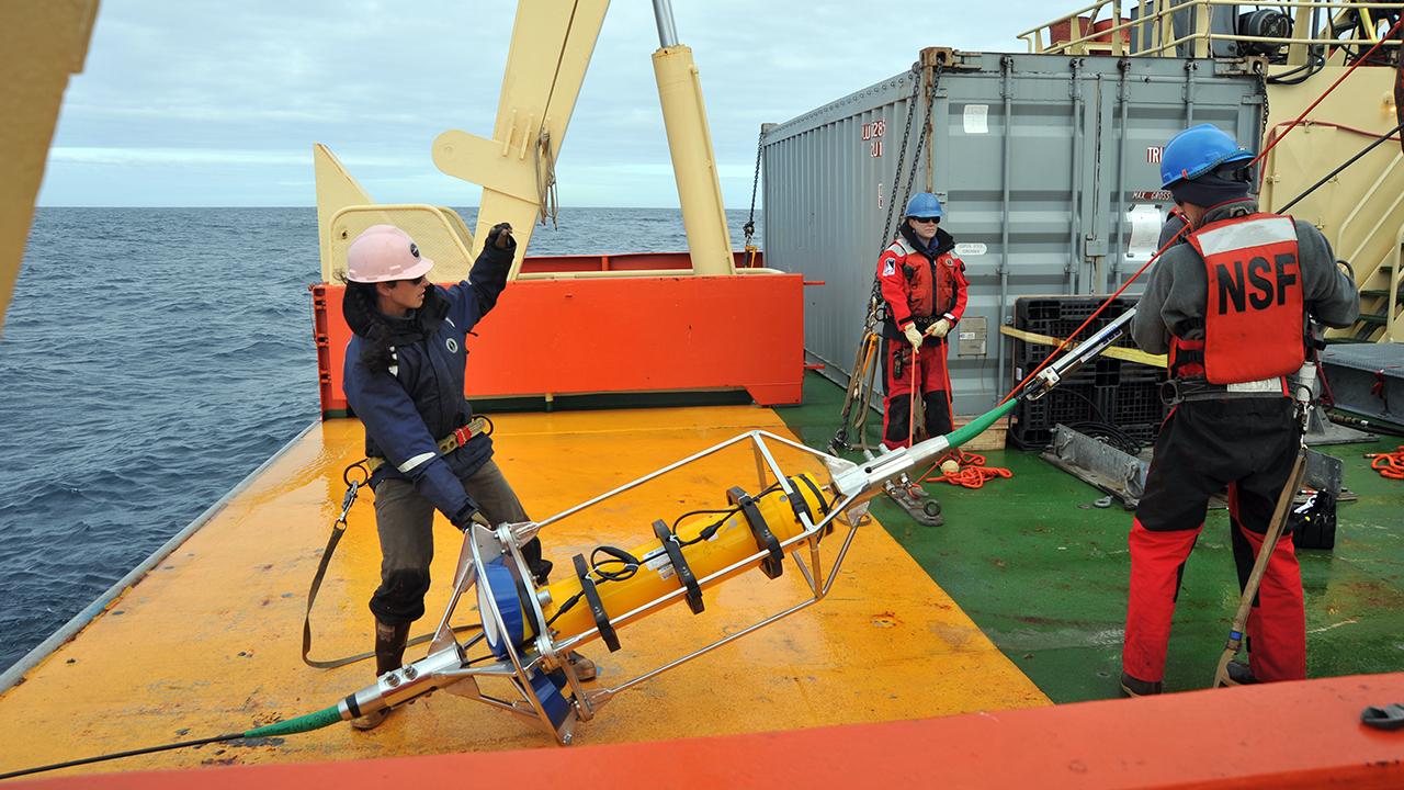 WHOI mooring technician Meghan Donohue deploys an ADCP.