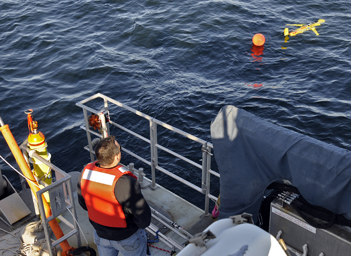 WHOI physical oceanographer Dave Fratantoni watches as a Slocum glider heads away from the ship during a test run