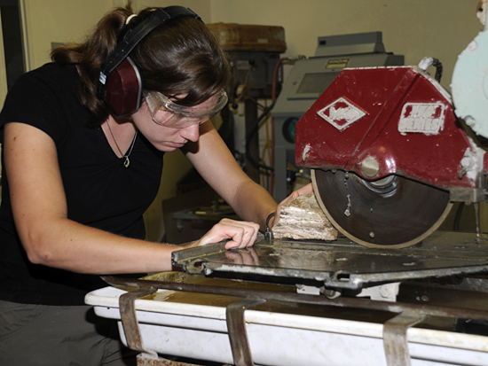 student cutting rock with table saw