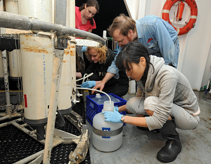 Crystal Breier, Kamila Stastna, Ken Buesseler, and Sachiko Yoshida (left to right) draw water from a rosette sampler in June 2011 on board the R/V Ka'imikai-o-Kanaloa.