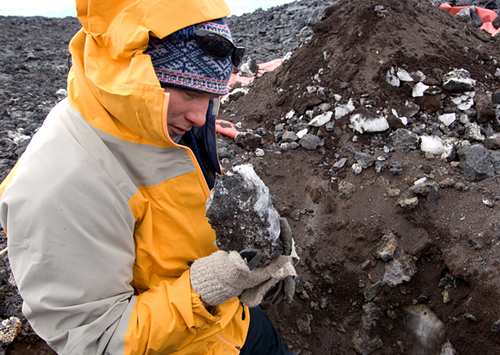 Adam Soule examining rock during Polar Discovery, Antarctica.