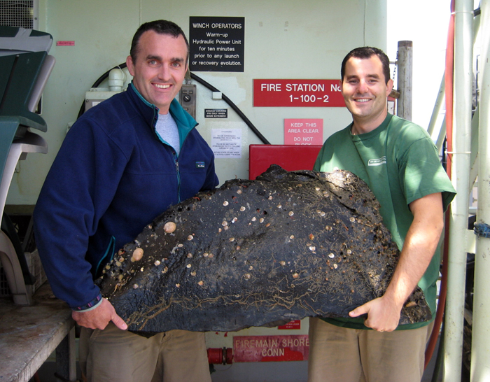 Chris Reddy (left) of WHOI and Chief Scientist Dave Valentine of UCSB hold a large chunk of undersea asphalt collected with one of the robotic arms of the DSV Alvin. The sample was surprising light in weight compared to rock.