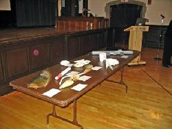 Image of long table on which are displayed samples of marine objects and oceanographic instruments